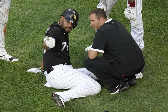 Chicago White Sox's Jose Abreu sits on the ground near home plate and talks with a member of the training staff, after Abreu ended up on the ground after Jake Lamb scored during the first inning of the team's baseball game against the Toronto Blue Jays on Wednesday, June 9, 2021, in Chicago. Abreu stayed in the game. (AP Photo/Charles Rex Arbogast)