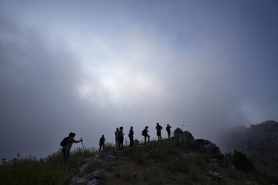 Lebanese and tourists' hikers trek in the mountains of Raachine village, in the Keserwan district, Mount Lebanon Governorate of Lebanon, Sunday, June 27, 2021. With their dollars trapped in the bank, a lack of functioning credit cards and travel restrictions imposed because of the pandemic, many Lebanese who traditionally vacationed over the summer at regional hotspots are also now turning toward domestic tourism. (AP Photo/Hassan Ammar)