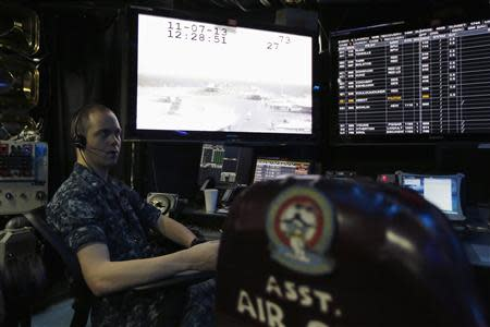 A U.S. Navy personnel works in the control room of the U.S. Navy aircraft carrier USS George Washington, during a tour of the ship in the South China Sea