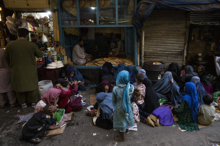 Afghan women and children sit in front of a bakery waiting for bread donations in Kabul's Old City, Afghanistan, Thursday, Sept. 16, 2021. (AP Photo/Bernat Armangue)