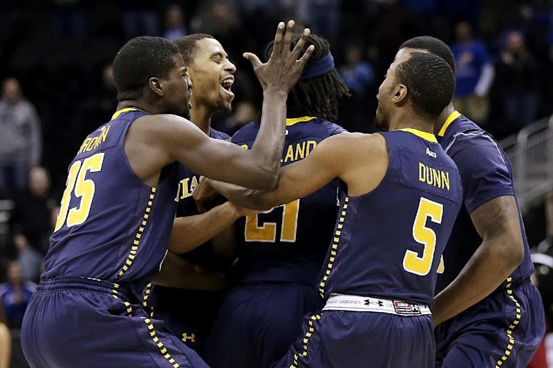 La Salle players including Rohan Brown (35), Tyrone Garland (21) and Taylor Dunn (5) celebrate after defeating Mississippi 76-74 in a third-round game of the NCAA college basketball tournament, Sunday, March 24, 2013, in Kansas City, Mo. (AP Photo/Charlie Riedel)