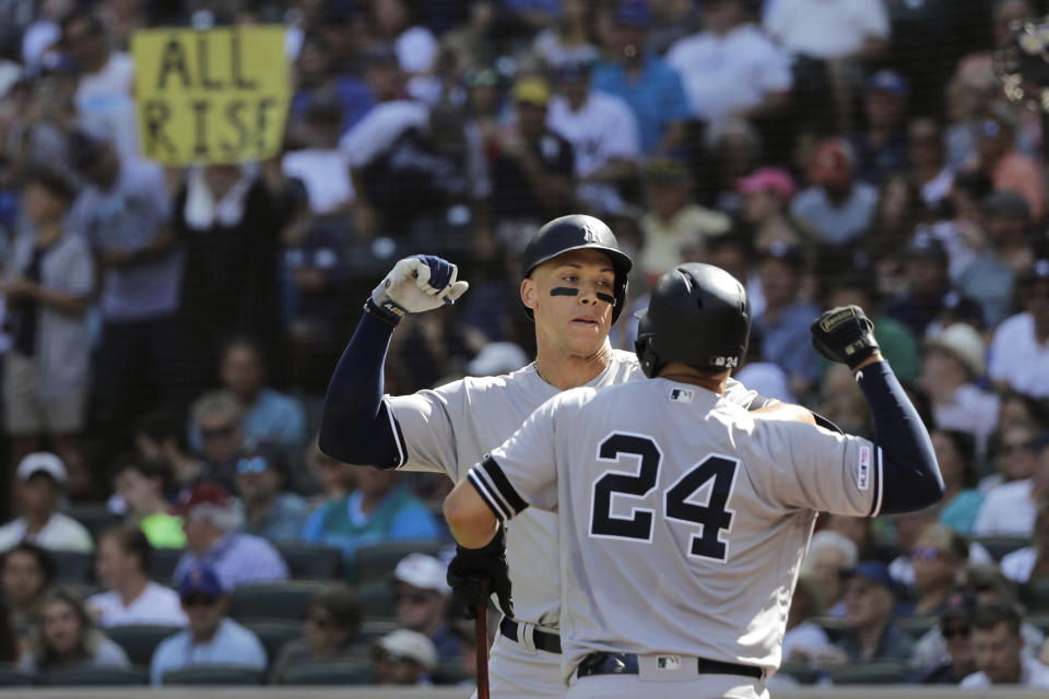 """A fan holds a sign that reads """"All Rise"""" as New York Yankees' Aaron Judge, left, greets Gary Sanchez (24) after Judge hit a two-run home run against the Seattle Mariners during the fifth inning of a baseball game, Wednesday, Aug. 28, 2019, in Seattle. (AP Photo/Ted S. Warren)"""
