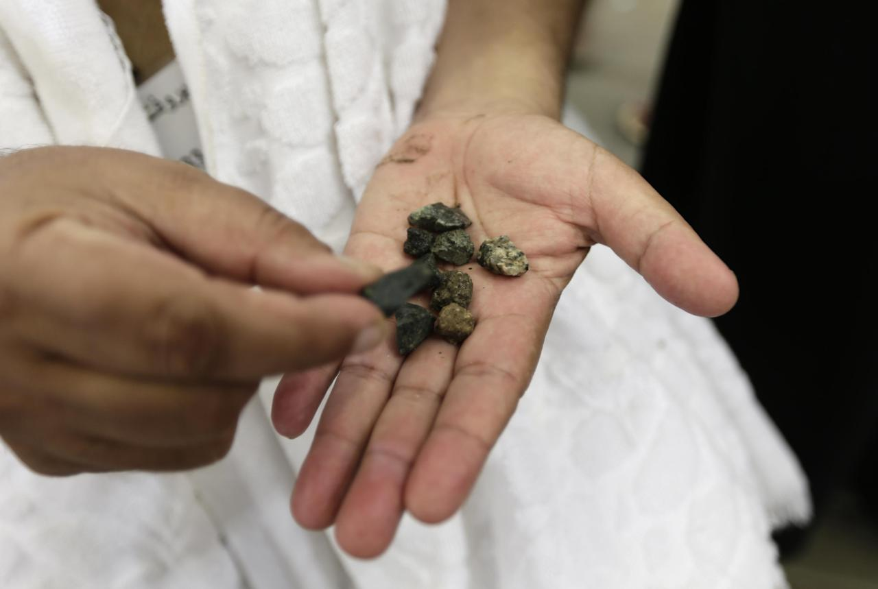 "A Muslim pilgrim collects stones to prepare to cast them at a stone pillar, symbolizing the stoning of Satan, in a ritual called ""Jamarat,"" the last rite of the annual hajj, in Mina near the Saudi holy city of Mecca, Saudi Arabia, Friday, Oct. 26, 2012. (AP Photo/Hassan Ammar)"
