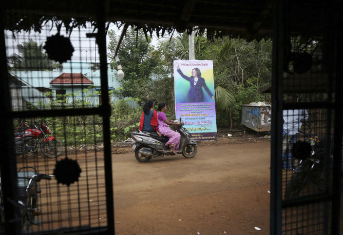 Village women ride past a banner featuring U.S. Vice President-elect Kamala Harris in Thulasendrapuram, the hometown of Harris' maternal grandfather, south of Chennai, Tamil Nadu state, India, Wednesday, Jan. 20, 2021. A tiny, lush-green Indian village surrounded by rice paddy fields was beaming with joy Wednesday hours before its descendant, Kamala Harris, takes her oath of office and becomes the U.S. vice president. (AP Photo/Aijaz Rahi)