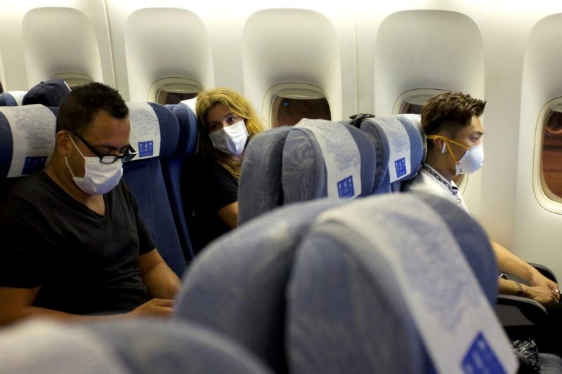 Passengers wearing masks sit on an Air China flight from Sydney to Beijing before takeoff, in Sydney