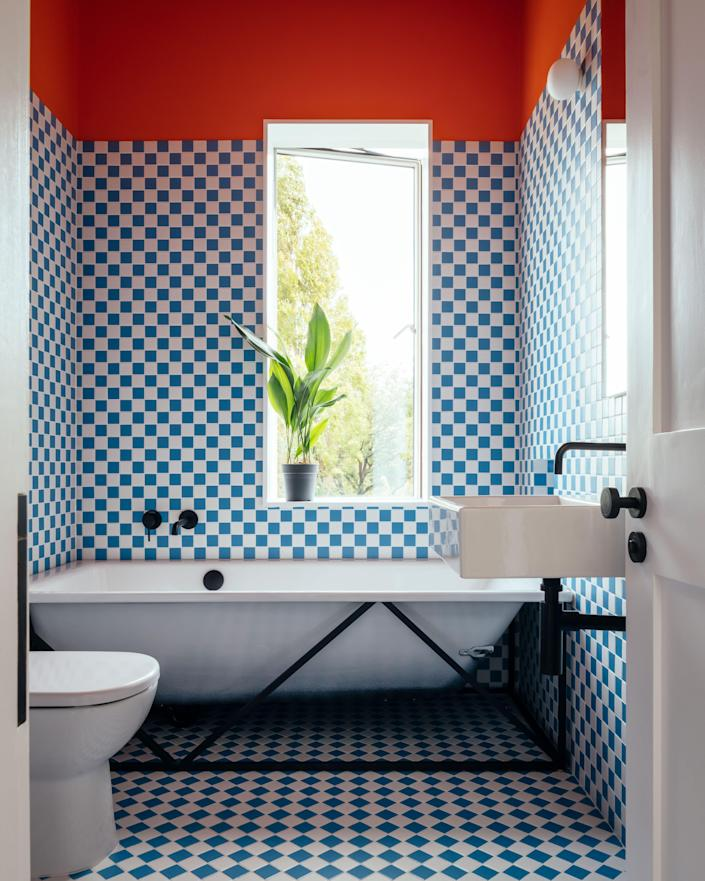The vibrant bathroom matches the downstairs energy.