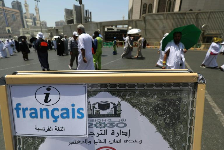 Muslim pilgrims walk past an information poster for a translation bureau in the Saudi holy city of Mecca on August 18, 2018, ahead of the start of the hajj pilgrimage
