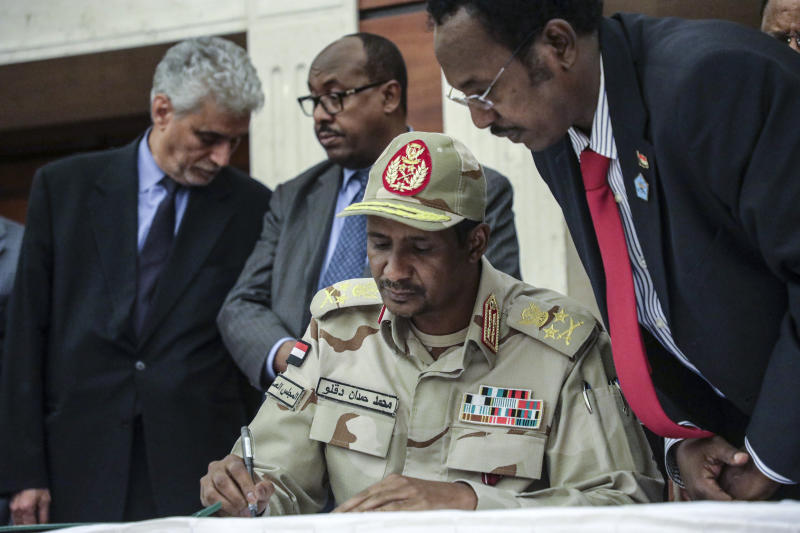 Gen. Mohammed Hamdan Dagalo signs a power sharing document with Sudan's pro-democracy movement and the ruling military council in Khartoum, Sudan, Wednesday, July 17, 2019. The two sides are still at work on a more contentious constitutional agreement that would specify the division of powers. (AP Photo/Mahmoud Hjaj)