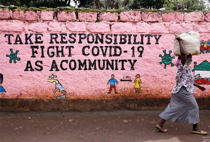"A woman walks past a mural whose slogan reads: ""Take responsibility, fight against Covid-19 as a community."""