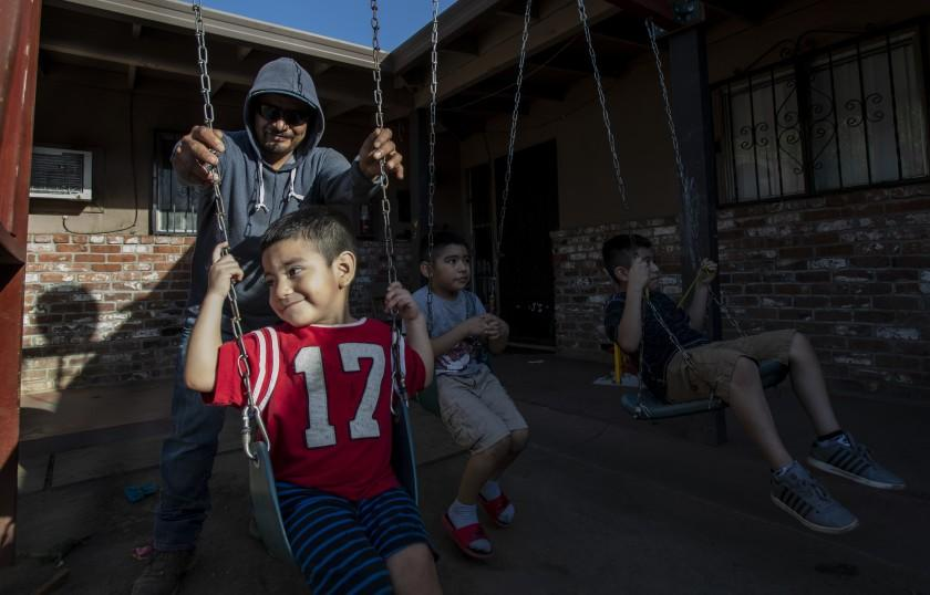 """STOCKTON, CA - OCTOBER 14, 2020: Farmworker Jose Luis Hernandez spends time with his sons Carlos, 2, Jose, 6, and Angel,9 outside their apartment on October 14, 2020 in Stockton, California. In normal times, Hernandez would have saved enough money from picking summer fruit in the California fields to make it through the slow winter months, but because of pandemic, his wages were cut and he isn't sure how he will provide food and shelter for his wife and three sons as the final grapes are taken from the vines. He's had to borrow money from a friend.""""I haven't saved anything. I am worried, """" he said.(Gina Ferazzi / Los Angeles Times)"""