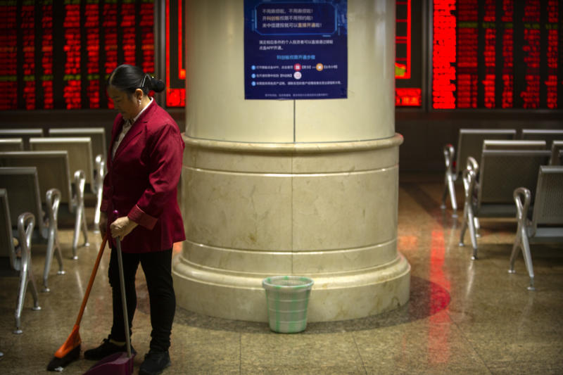 A cleaner sweeps the floor at a stock brokerage house in Beijing, Tuesday, Nov. 19, 2019. Asian shares were mixed Tuesday as investor sentiment remained cautious amid worries about the next development in trade talks between the United States and China. (AP Photo/Mark Schiefelbein)