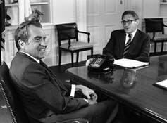 Nixon sits at his desk in the Oval Office smiling as Kissinger sits in front of the desk.