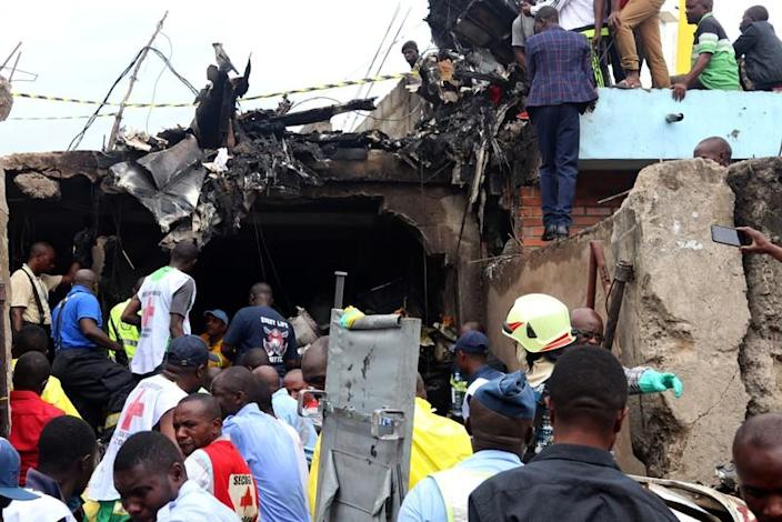 Rescuers and civilians gather at the accident scene of a plane Dornier 228-200 plane operated by local company Busy Bee that crashed into a densely populated neighborhood in Goma
