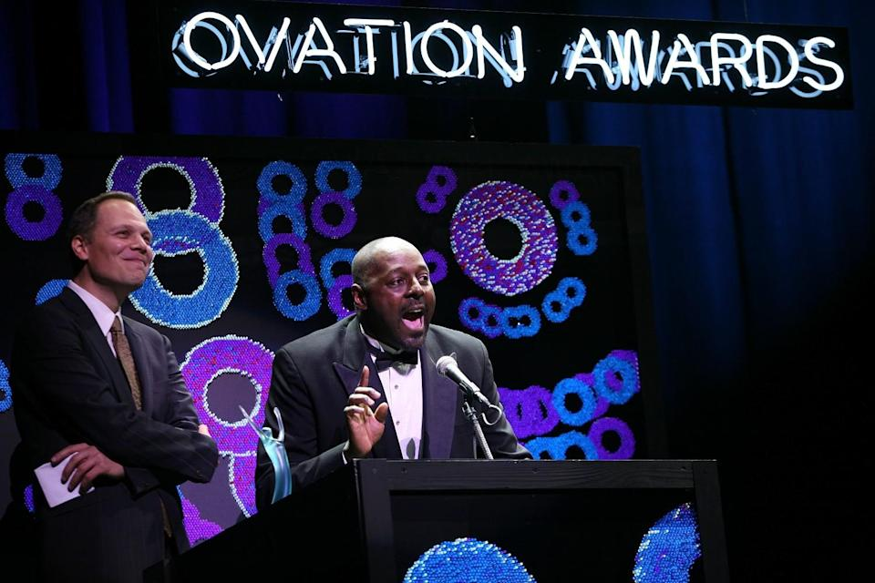 """Michael Shepperd, alongside David Tarlow, speaks into a microphone on a stage with the sign """"Ovation Awards."""""""