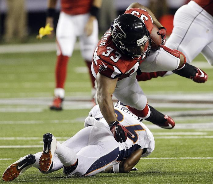 Atlanta Falcons running back Michael Turner (33) is hit by Denver Broncos free safety Rahim Moore (26) during the first half of an NFL football game, Monday, Sept. 17, 2012, in Atlanta. (AP Photo/John Bazemore)