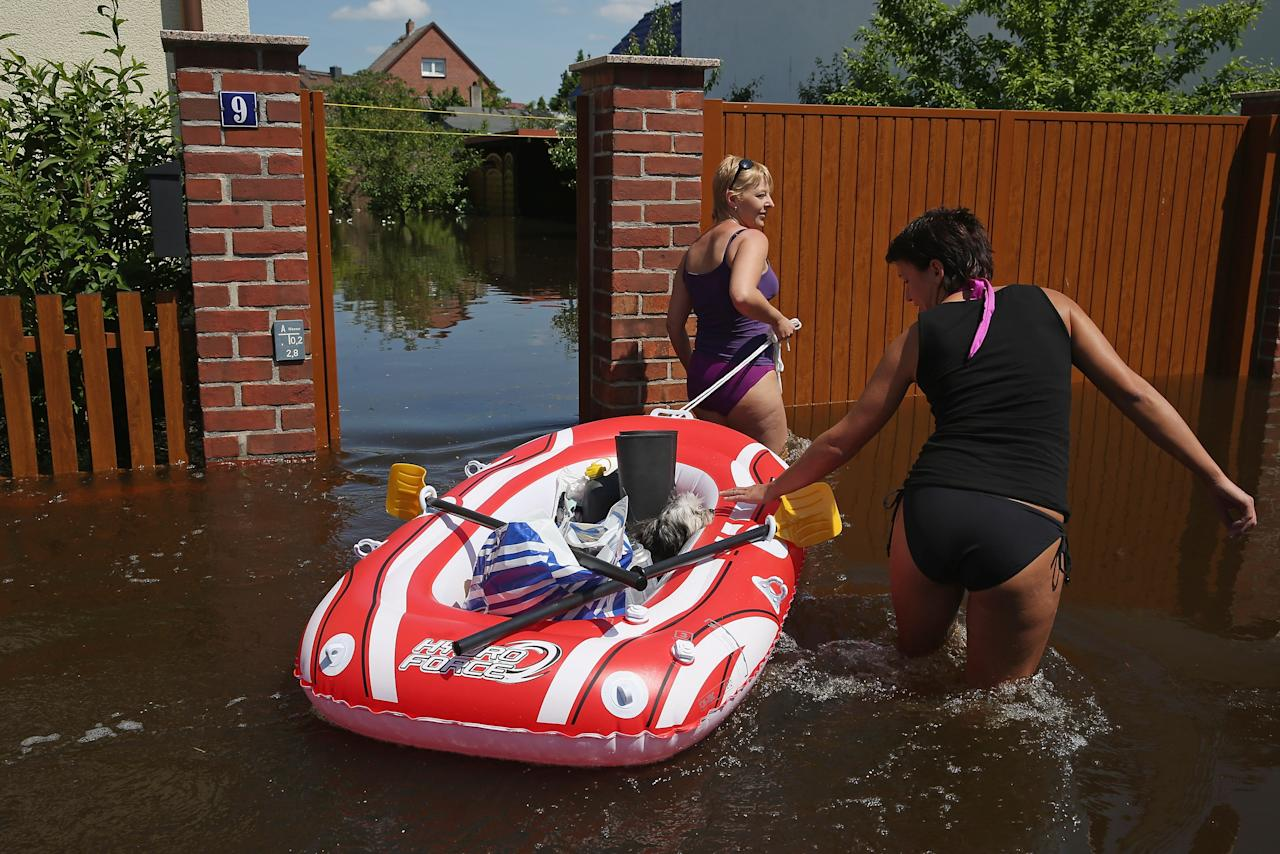 ELSTER, GERMANY - JUNE 07: Friends Stephanie (R) and Sandra transport Stephanie's dog Chewbaca, groceries and bottles of butane in a rubber raft through a flooded street to Sandra's home near the swollen Elbe river on June 7, 2013 in Elster, Germany. Floodwaters that have devastated parts of Saxony and Thuringia are now moving north, threatening towns along the Elbe and Saale rivers all the way to Hamburg. Eastern and southern Germany are suffering under floods that in some cases are the worst in 400 years. At least four people are dead and tens of thousands have evacuated their homes. (Photo by Sean Gallup/Getty Images)