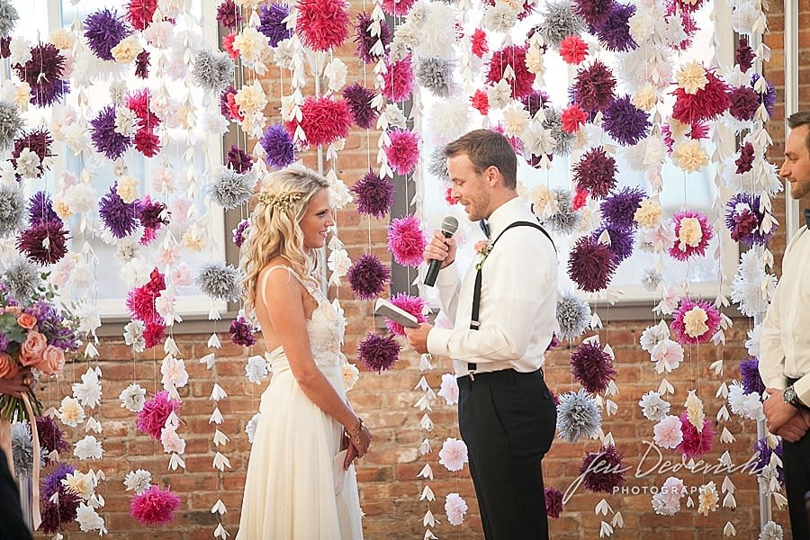 <p><i>An already-married couple renew their vows among strangers in front of a decadent floral background. (Photo: Jen Dederich Photography via The Big Fake Wedding)</i></p>