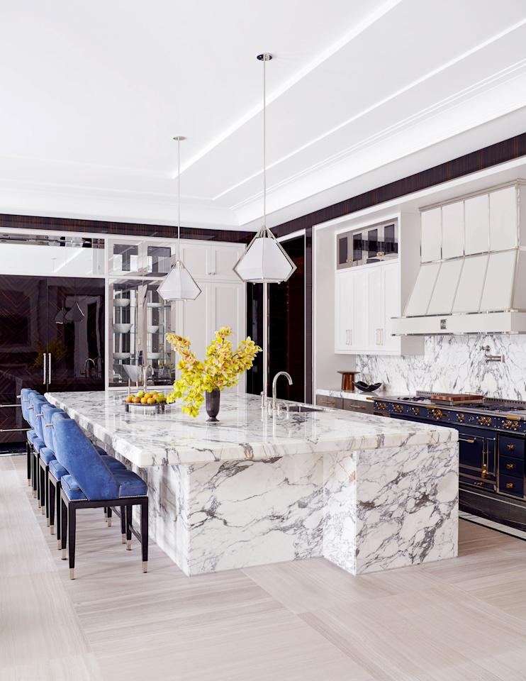 "Suede chairs by <a href=""http://ferrisrafauli.com/"">Rafauli</a> line a Paonazzo marble island in the kitchen. <a href=""https://www.gabriel-scott.com/"">Gabriel Scott</a> pendants; <a href=""https://www.lacornueusa.com/"">La Cornue</a> x Ferris Rafauli range; <a href=""https://www.us.kohler.com/us/"">Kohler</a> sinks; <a href=""Waterworks"">Waterworks</a> fittings."