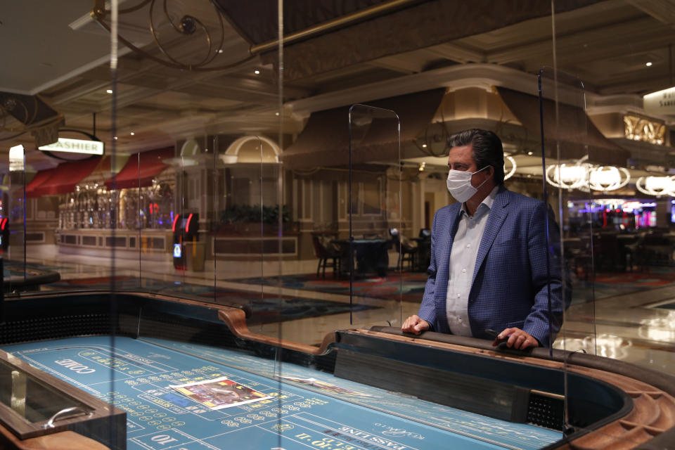 Bill Hornbuckle, acting CEO and president of MGM Resorts International, stands between acrylic barriers used as a coronavirus safety precaution at a craps table in the closed Bellagio hotel and casino, Wednesday, May 20, 2020, in Las Vegas. Casino operators in Las Vegas are awaiting word when they will be able to reopen after a shutdown during the coronavirus outbreak. (AP Photo/John Locher)