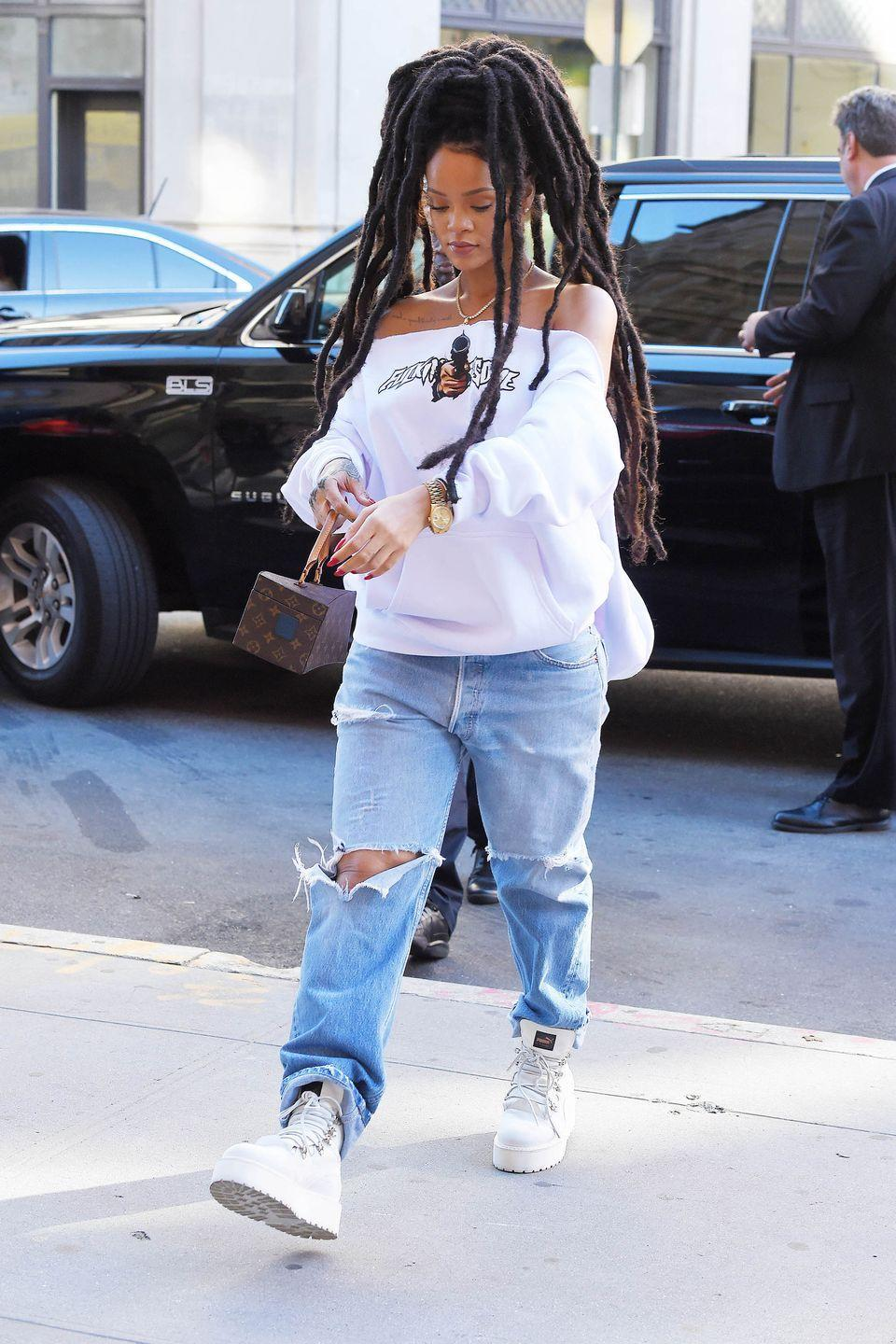 <p>In an off-the-shoulder white sweatshirt, ripped baggy jeans, white platform Puma boots Louis Vuitton bag and gold watch while out in New York City. </p>
