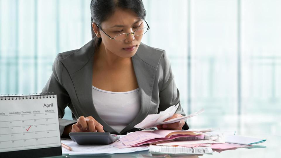Finishing calculation for tax form on April 15 concept, with calendar in front of an accountant.