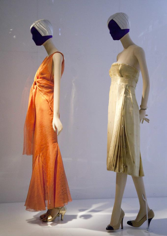 """A 1935 evening dress, left, by Elsa Schiaparelli, and a 2004 dress by Miuccia Prada are are on display at the Metropolitan Museum of Art, Monday, May 7, 2012 in New York. The show """"Schiaparelli and Prada, Impossible Conversations,"""" opens May 10 and continues through Aug. 19. (AP Photo/Mark Lennihan)"""