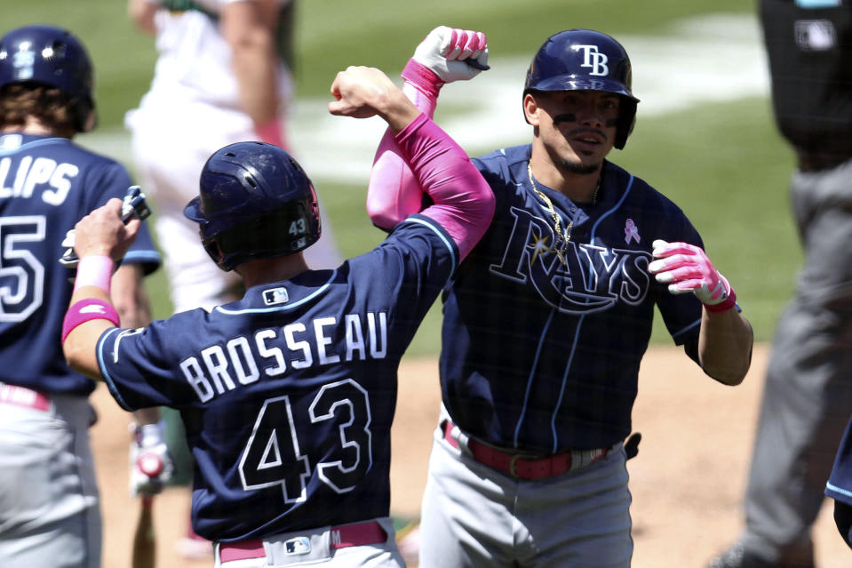 Tampa Bay Rays' Willy Adames, right, is congratulated by teammate Mike Brosseau after hitting a three-run home run against the Oakland Athletics during the fifth inning of a baseball game in Oakland, Calif., Sunday, May 9, 2021. (AP Photo/Jed Jacobsohn)