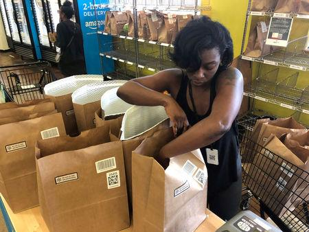 A Whole Foods shopper prepares a delivery order at the grocerÕs Rockwood Commons store in Cincinnati
