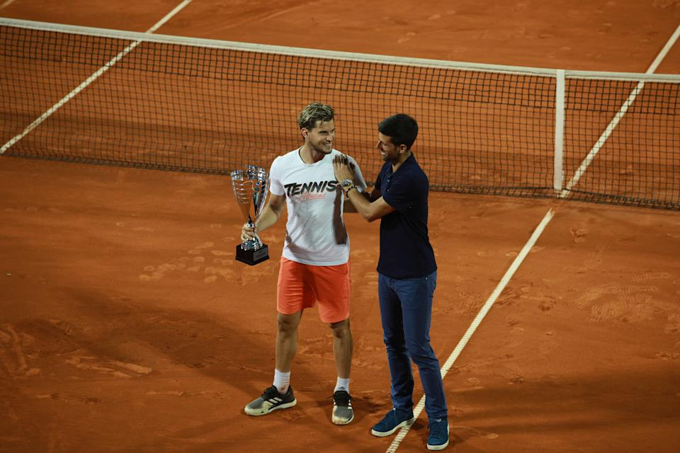 Dominic Thiem (pictured left) holds the trophy next to Novak Djokovic (pictured right) who congratulates him.