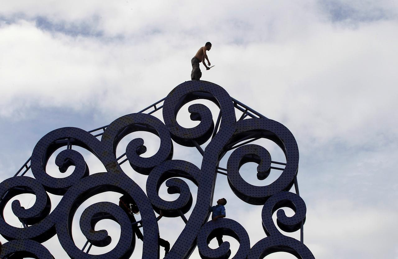 "A police officer and a firefighter try to stop Julio Lopez, who is carrying a knife in his hand, during his suicide attempt on top of the ""Tree of Life"" metal sculpture in Managua, Nicaragua July 27, 2017. REUTERS/Oswaldo Rivas     TPX IMAGES OF THE DAY"
