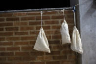 Bats, inside cloth bags, hang from a line at Brazil's state-run Fiocruz Institute at Pedra Branca state park, near Rio de Janeiro, Tuesday, Nov. 17, 2020. A 2019 study found that of viruses originating from the five most common mammalian sources — primates, rodents, carnivores, ungulates and bats — those from bats are the most virulent in humans. (AP Photo/Silvia Izquierdo)