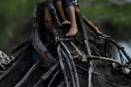 The feet of an Indigenous girl from the Parintintin tribe are seen as she sits on a cut tree trunk in Traira village near Humaita
