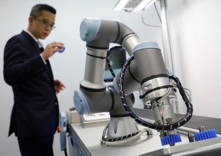A Universal Robots employee demonstrates how a model of their industrial robot arms works in Singapore