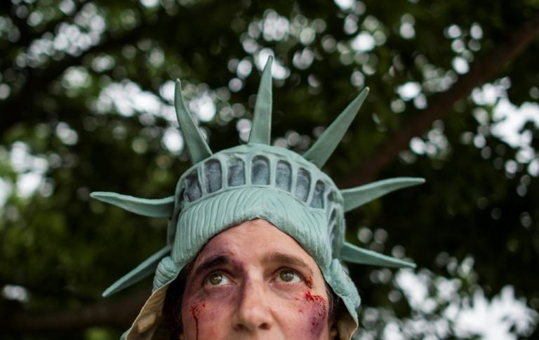 A protester dressed as the Statue of Liberty looks on during a rally speaking out against social injustice and poverty, on the National Mall in Washington, DC (AFP Photo/Andrew CABALLERO-REYNOLDS)