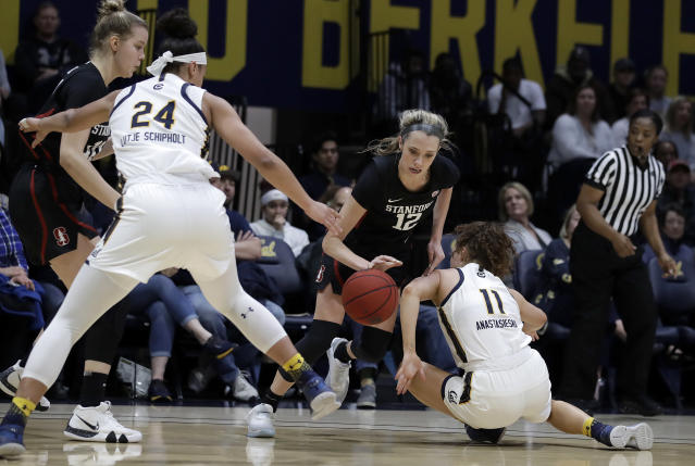 Stanford's Lexie Hull, center, controls the ball between California's Evelien Lutje Schipholt (24) and Sara Anastasieska (11) in the first half of an NCAA college basketball game Sunday, Jan. 12, 2020, in Berkeley, Calif. (AP Photo/Ben Margot)