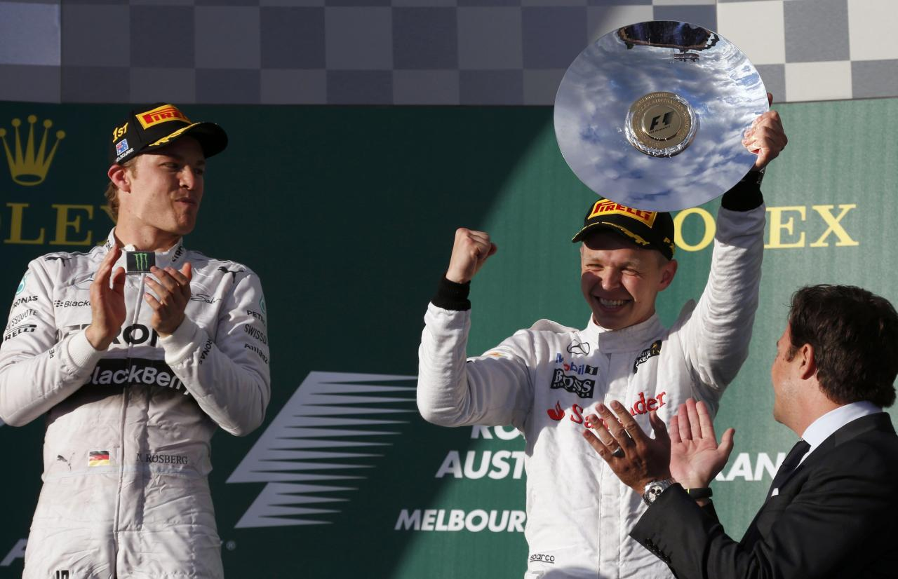 Third-placed McLaren Formula One driver Kevin Magnussen of Denmark (R) lifts his trophy on the podium as winner Mercedes Formula One driver Nico Rosberg of Germany claps his hands after the Australian F1 Grand Prix at the Albert Park circuit in Melbourne March 16, 2014. REUTERS/David Gray (AUSTRALIA - Tags: SPORT MOTORSPORT F1)