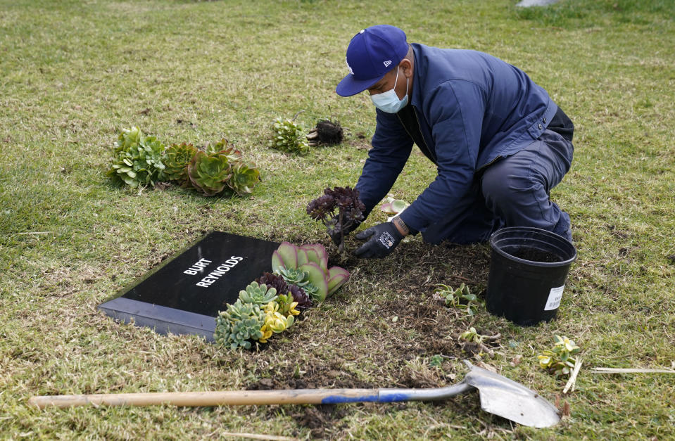 Francisco Ventura, an employee at Hollywood Forever cemetery, places flowers around a temporary headstone for the late actor Burt Reynolds in the Garden of Legends section of the cemetery, Thursday, Feb. 11, 2021, in Los Angeles. Reynolds' cremated remains were moved from Florida to Hollywood Forever, where a small ceremony was held Thursday. A permanent gravesite will be put up for Reynolds in a few months. (AP Photo/Chris Pizzello)