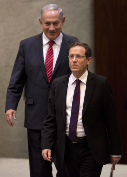 "In this photo taken on Monday, Jan. 20, 2014, Israel's opposition leader and Labor Party leader Isaac Herzog, front, walks past Israeli Prime Minister Benjamin Netanyahu at the Knesset, Israel's Parliament, in Jerusalem. Israel's opposition leader said Tuesday that Prime Minister Benjamin Netanyahu fully appreciates the wisdom of making peace with the Palestinians. He's just not sure he has the ""guts."" Herzog, who was elected head of the Labor Party in November, said that his ultimate goal is to replace Netanyahu. But he said he would back the prime minister if he genuinely pursues peace with the Palestinians and offered a political ""safety net"" should Netanyahu's right-leaning coalition rebel in case of substantial progress in recently restarted peace talks.(AP Photo/Ariel Schalit)"