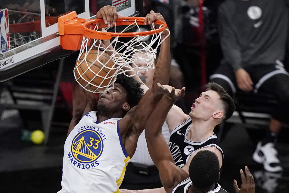 James Wiseman (33) dunks in front of Brooklyn Nets forward Rodions Kurucs, right, during the second half of an opening night NBA basketball game, Tuesday, Dec. 22, 2020, in New York. (AP Photo/Kathy Willens)