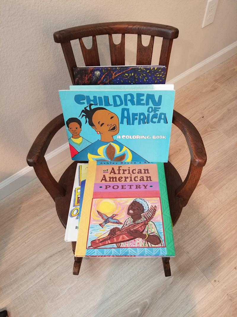 """Children of Africa"" was published by Drum and Spear Press. Daphne Muse, who worked there, is passing it on to her 14-month-old great-grandson Mason who has a library of more than 300 books. The rocking chair belonged to Muse's great-grandmother Daphne Allen when she was a child circa the 1870s."