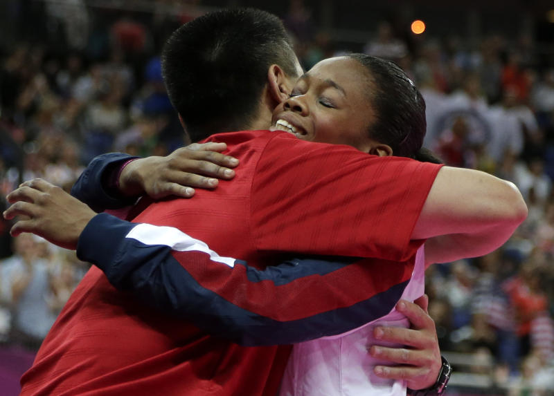 U.S. gymnast and gold medallist Gabrielle Douglas is hugged by coach Liang Chow during the artistic gymnastics women's individual all-around competition at the 2012 Summer Olympics, Thursday, Aug. 2, 2012, in London. (AP Photo/Gregory Bull)