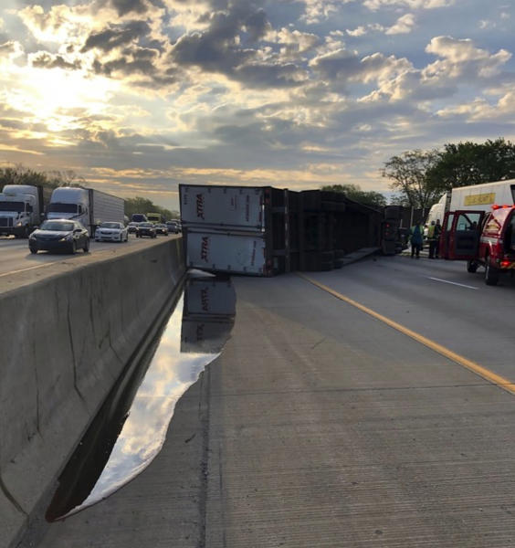 This photo released by the Indiana State Police shows a semi-trailer hauling honey overturned on a northwestern Indiana highway, spilling some of the sticky substance and restricting travel for hours in Hammond, Ind., Wednesday, May 15, 2019. State police say the truck was hauling about 41,000 pounds of amber honey along Interstate 80/94 when the driver lost control and the truck overturned. At least four containers of honey were leaking and mixing with diesel fuel from the overturned vehicle. (Indiana State Police via AP)