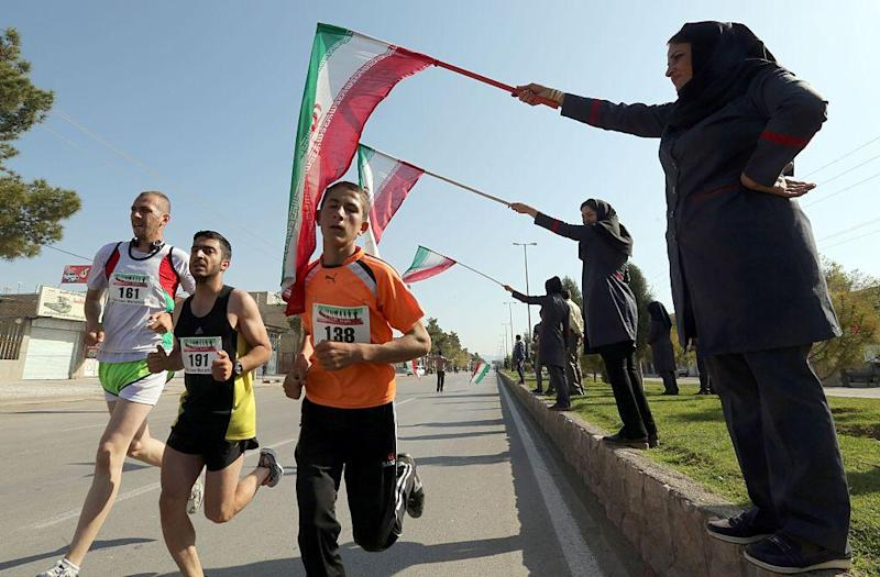 Iranian women wave their national flag as they support Iranian and foreign runners competing in Iran's first internation marathon in Marvdasht on April 9, 2016: AFP/Getty Images