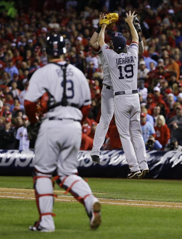 Boston Red Sox catcher David Ross (3) watches as relief pitcher Koji Uehara celebrates with Mike Napoli after defeating the St. Louis Cardinals 4-2 in Game 4 of baseball's World Series Sunday, Oct. 27, 2013, in St. Louis. (AP Photo/Matt Slocum)