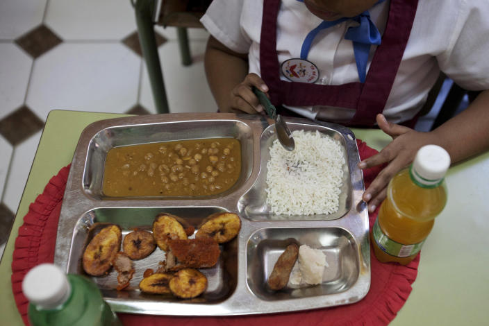 Milagro Ramos, a student at the Angela Landa elementary school, spoons up rice from her lunch tray, which also contains a chicken croquette, a piece of taro root and yellow pea soup in Old Havana, Cuba, Tuesday, May 6, 2014. Milagro brought fried plantains, lower left corner of her tray, and an orange drink from home. The children provide their own drinks. (AP Photo/Franklin Reyes)