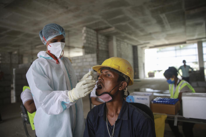 A health worker collects a swab sample from a laborer to test for COVID-19 at a construction site in New Delhi, India, Thursday, June 10, 2021. India's economy was on the cusp of recovery from the first pandemic shock when a new wave of infections swept the country, infecting millions, killing hundreds of thousands and forcing many people to stay home. Cases are now tapering off, but prospects for many Indians are drastically worse as salaried jobs vanish, incomes shrink and inequality is rising. (AP Photo)
