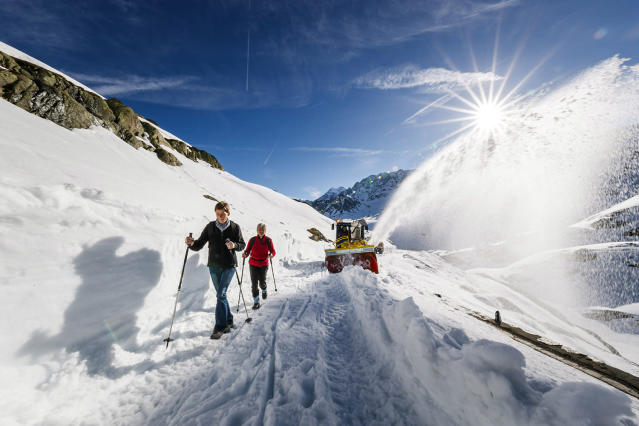 <p>People walk past a snow plough as it clears snow off the road at the Great St. Bernard pass, Switzerland, May 16, 2017. The snow ploughs and snow blowers make their way slowly through the mountain every spring and will have carved through layers several meter-deep during a four-week operation this year. The Col du Grand-Saint-Bernard, in French, is the third highest road pass of Switzerland and connects the canton of Valais to Italy. (Photo: Valentin Flauraud/EPA </p>