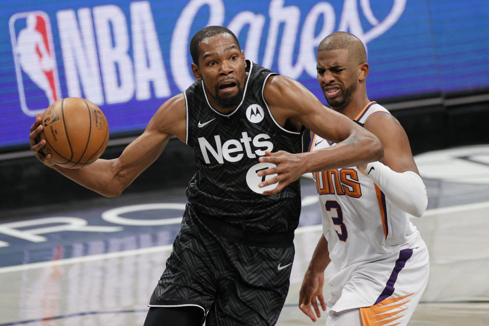 Kevin Durant of the Brooklyn Nets drives to the basket as Chris Paul of the Phoenix Suns defends