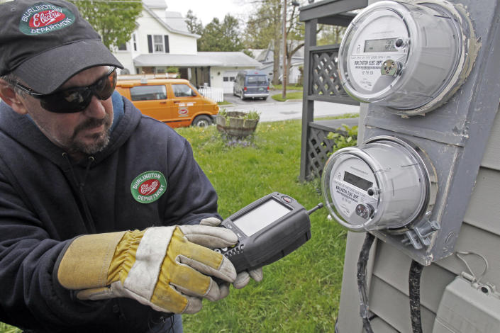 """Mark Delbeck of Burlington Electric, checks the radio frequency of a newly-installed """"smart"""" meter on Thursday, May 10, 2012, in Burlington, Vt. Vermont has become a hotbed in the debate over possible health effects and damage to privacy from a new generation of """"smart"""" electric meters, wth lawmakers passing a measure to block utilities from charging customers for not having them. It's possible Vermont is the first state to not charge customers to """"opt-out.""""(AP Photo/Toby Talbot)"""