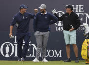 United States' Bryson DeChambeau, left, greets United States' Phil Mickelson, right behind Spain's Jon Rahm as they wait to play on the 1st tee during a practice round for the British Open Golf Championship at Royal St George's golf course Sandwich, England, Wednesday, July 14, 2021. The Open starts Thursday, July, 15. (AP Photo/Ian Walton)